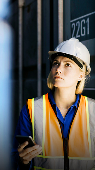 Blonde woman in high vis jacket looking at phone photograph