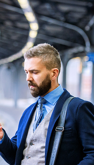 Business man looking at phone in station photograph