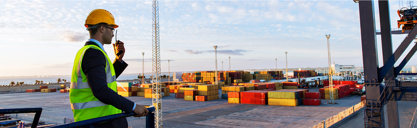 Man in high vis jacket with walkie talkie looking down on containers photograph