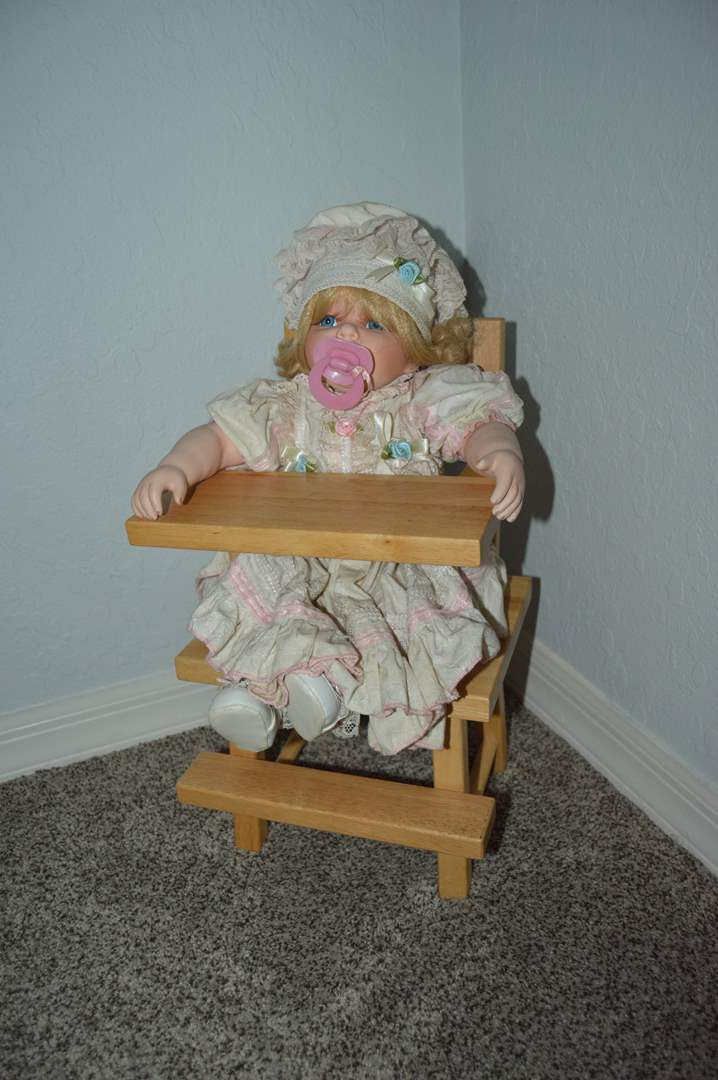 Lot # 108 Porcelain baby doll in wood doll highchair - Numbered (main image)